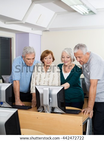 Senior Men And Women Using Computer In Class