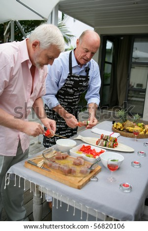 Senior men preparing fish kebabs on a terrace - stock photo
