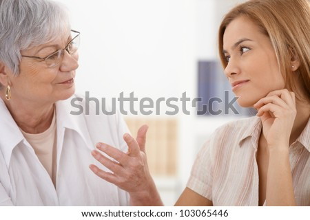 Senior mother and attractive daughter looking at each other with affection, talking, smiling. - stock photo