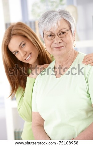 Senior mother and attractive young daughter smiling happily, looking at camera.?