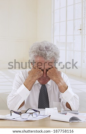 Senior nan at desk in shirt and tie looking depressed, holding his head and worrying about money and bills - stock photo