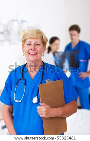 senior nurse with clipboard in hospital, background is her young colleagues - stock photo