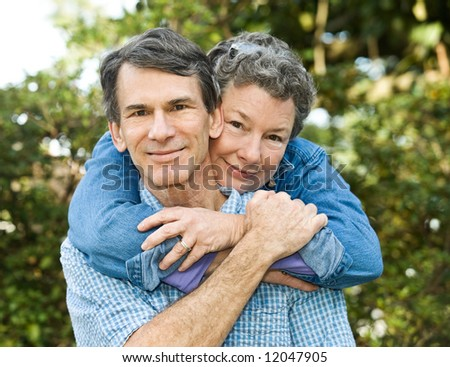 Senior or middle age couple outdoors hugging, sharing an affectionate moment. - stock photo