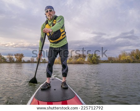senior paddler in life jacket enjoying stand up paddling on lake, fall scenery in Fort Collins, Colorado - stock photo