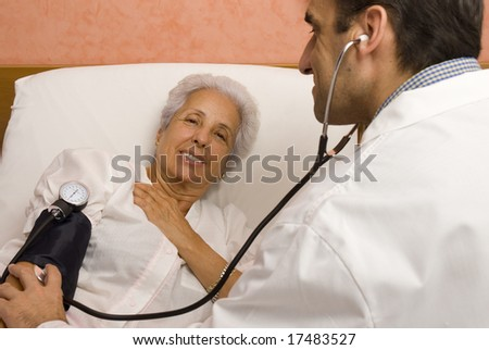 Senior patient is being observed by doctor - measuring blood pressure - stock photo