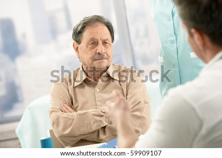 Senior patient listening to doctor's explanation on consultation.? - stock photo