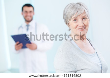 Senior patient looking at camera with doctor on background  - stock photo