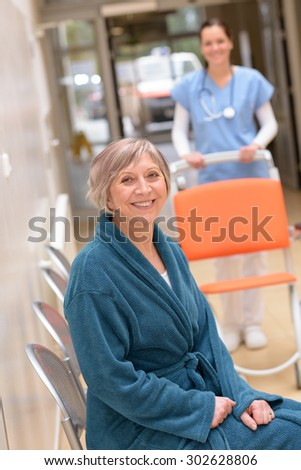 Senior patient sitting in hospital waiting for nurse with wheelchair - stock photo