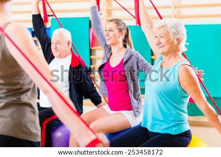 Senior people at fitness course in gym exercising with stretch band - stock photo