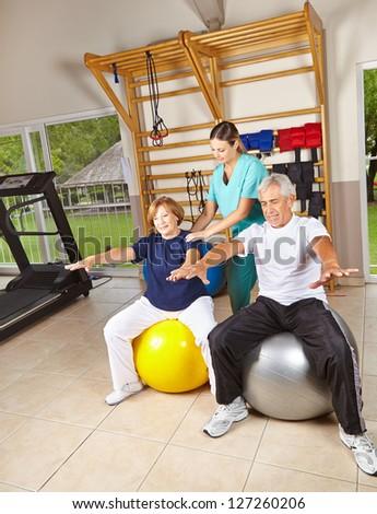 Senior people doing rehab gymnastics on gym balls - stock photo
