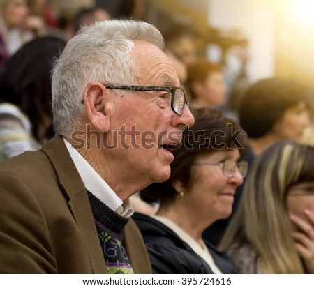 Senior people in the audience. Excited old man watching performance with open mouth - stock photo