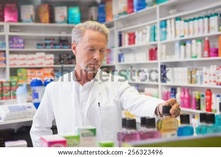 Senior pharmacist looking a medicine in the pharmacy - stock photo