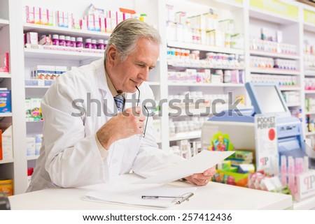 Senior pharmacist reading prescription in the pharmacy - stock photo