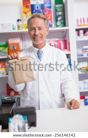Senior pharmacist showing a envelope in the pharmacy