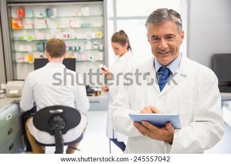 Senior pharmacist using tablet pc at the hospital pharmacy - stock photo