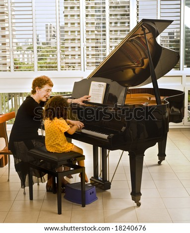 senior piano teacher with young girl student - stock photo