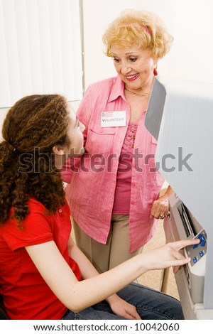 Senior polling place volunteer helping a young voter. - stock photo