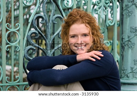 Senior Portrait of redhead female HS  student in front of weathered patina copper works. - stock photo