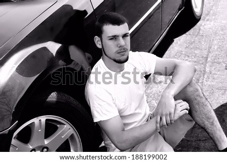 Senior portrait of young male sitting by his car in black and white - stock photo