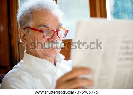 senior reading newspaper at home