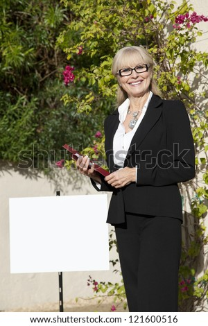 Senior real estate agent standing by signboard - stock photo