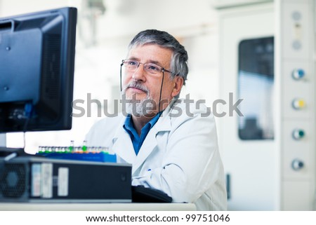Senior researche rusing a computer in the lab while working on an experiment (color toned image) - stock photo
