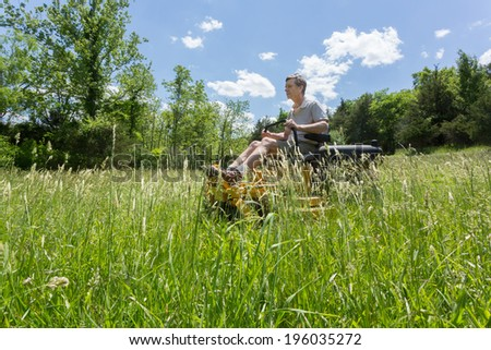 Senior retired male cutting very deep grass in a meadow or field after leaving it to grow for far too long before cutting. He is mowing sideways to the camera using yellow zero-turn lawn mower - stock photo