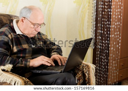 Senior retired man sitting in a comfortable armchair typing on his laptop computer which he has balanced on his lap - stock photo