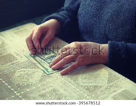 Senior retired woman with small amount of money on table, toned image, colorized, selective focus, very shallow dof. Hand with money american dollars. Wrinkle senior hand touch dollar cash on table - stock photo