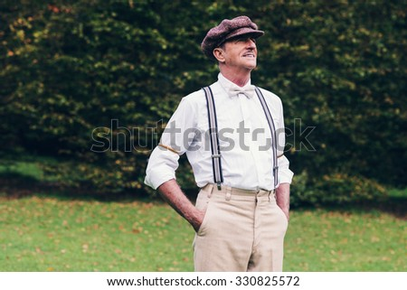 Senior retro fashion man standing in garden. - stock photo