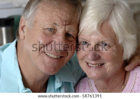 Senior romantic couple shares some intimate moments at their home. - stock photo