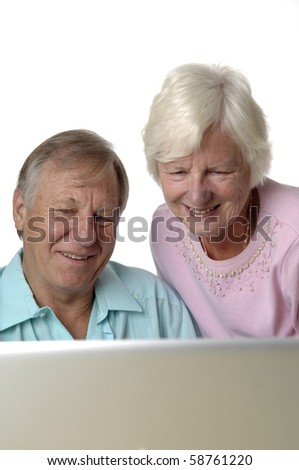 Senior romantic couple uses computer and the Internet to do some e-banking from their rural home. - stock photo