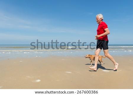 Senior runner with dog at the beach - stock photo