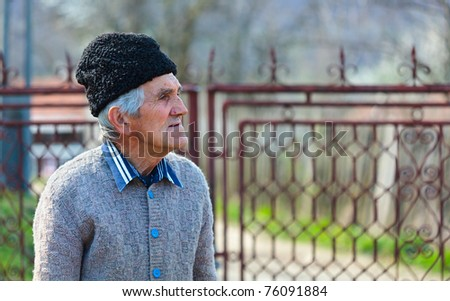 Senior rural man outdoor, near a gate - stock photo
