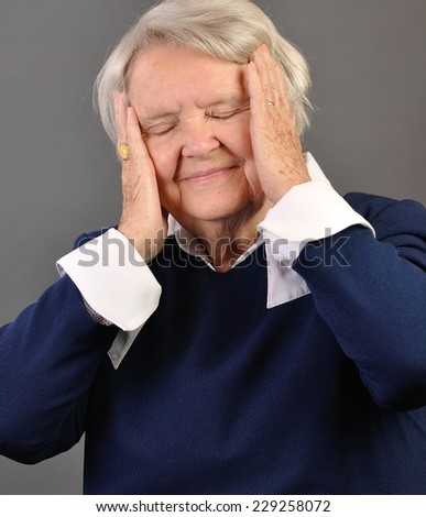 Senior sad woman with grey hairs against grey background.