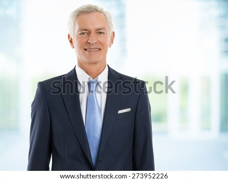 Senior sales man looking at camera and smiling while standing at office. - stock photo