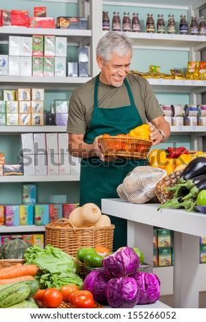 Senior salesman working in grocery store - stock photo
