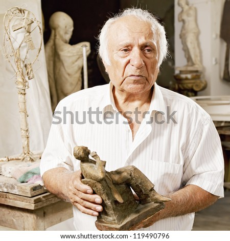 Senior sculptor holding his sculpture and looking sideways - stock photo