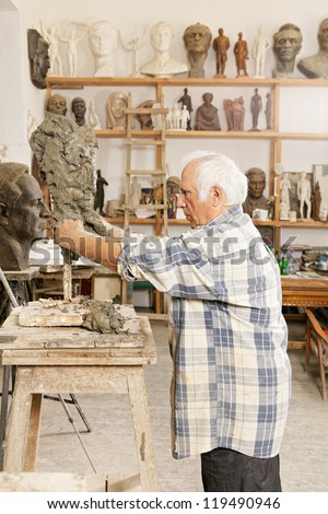 Senior sculptor making sculpture putting clay on wire skeleton profile view - stock photo