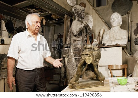 Senior sculptor showing his works in workshop - stock photo