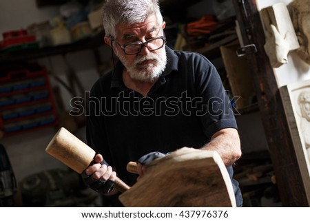 Senior sculptor working on his sculpture in his workshop. - stock photo