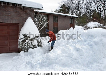 Senior shoveling his walkway after a winter snowstorm - stock photo