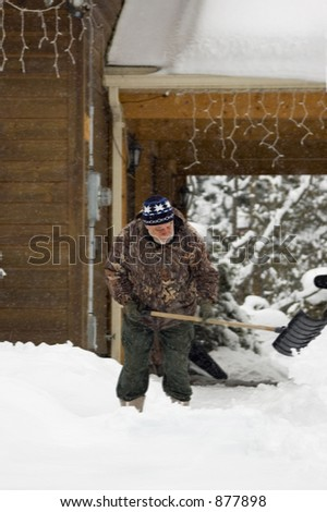 Senior shovelling snow off its driveway on a stormy day - stock photo