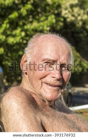 senior sits in the chair in the garden and enjoys the sun - stock photo