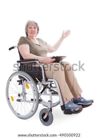 Senior sitting in wheelchair pointing to the side while holding tablet device. All on white background.