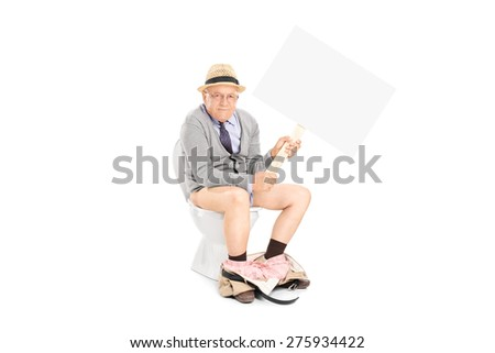 Senior sitting on a toilet, holding a big blank signboard and looking at the camera isolated on white background - stock photo