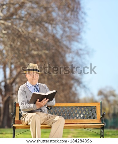 Senior sitting on bench and reading a book in park shot with tilt and shift lens - stock photo