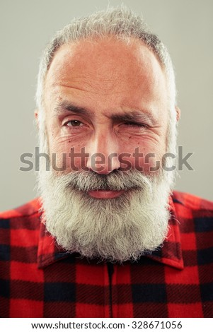senior smiley man with grey-haired beard looking at camera and winking over light grey background - stock photo