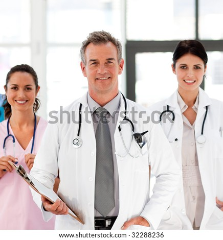Senior Smiling doctor with his colleagues in front of the camera - stock photo