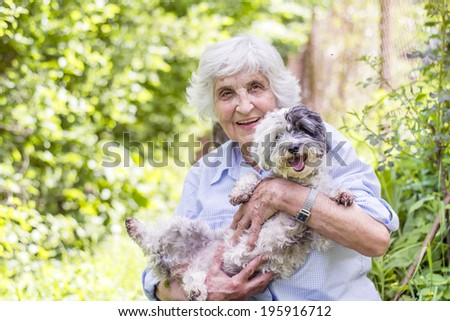 Senior smiling woman hugging her dog in the mountain - stock photo